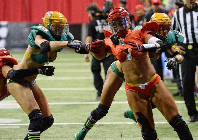 Danika Brace #8 of the Las Vegas Sin breaks tackles by Anna Heasman #13 and Laurie Gelis-Diaz #11 of the Green Bay Chill to score a touchdown during their game at the Thomas & Mack Center on May 15, 2014 in Las Vegas, Nevada. Las Vegas won 34-24. (Photo by Ethan Miller/Getty Images)
