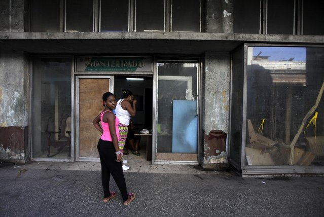 A woman stands in front of at a store which has converted into a house in Havana February 23, 2015. (Photo by Enrique De La Osa/Reuters)