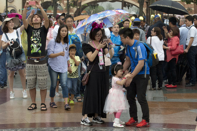 A child asks to be carried during a crowded opening day at the Disney Resort in Shanghai, China, Thursday, June 16, 2016. (Photo by Ng Han Guan/AP Photo)