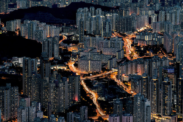 """Motherboard City. """"Hong Kong has one of the highest population densities in the world. This city is full of sky-high buildings, yet surrounded by lots of mountains. If you go up to the top, you will see a motherboard like structural design of the whole city. The buildings seem like computer servers, whereas the main roads are the connecting cables of different servers. People are like data, transferring from one side to another side"""". (Photo by Ho Lam Cheng/NatGeo Cities Travel Photographer of the Year 2017)"""