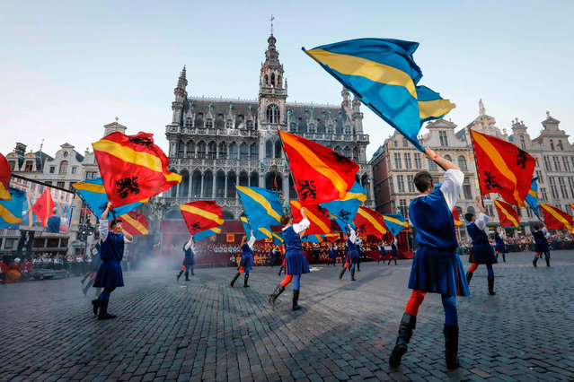 """People wave flags as they perform during an historical parade """"Ommegang"""" celebrating Charles Quint coming to Brussels in 1549, in downtown Brussels on July 5, 2017. (Photo by Thierry Roge/AFP Photo/BELGA)"""