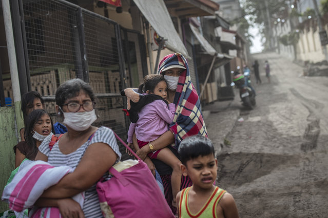 Residents fleeing Taal Volcano's eruption wait for a ride on the side of a highway on January 13, 2020 in Lemery, Batangas province, Philippines. The Philippine Institute of of Volcanology and Seismology raised the alert level to four out of five, warning that a hazardous eruption could take place anytime, as Manila's international airport suspended flights and authorities began evacuating tens of thousands of people from the area. (Photo by Ezra Acayan/Getty Images)