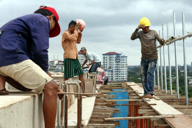 Workers gather on top of a construction site in Yangon, Myanmar, 16 June 2016. Asian Development Bank (ADB) has announced to expend it's annual sovereign concessional lending for Myanmar's projects from about USD 150 millions to USD 350 millions starting from 2017. ADB expects Myanmar's economy to grow at 8.4% in the fiscal year 2016-2017, the fiscal year which will ends on 31 March 2017. And 8.3% in 2017-2018 after slowing to 7.2% due to devastating floods and landslides during 2015-2016. (Photo by Lynn Bo Bo/EPA)