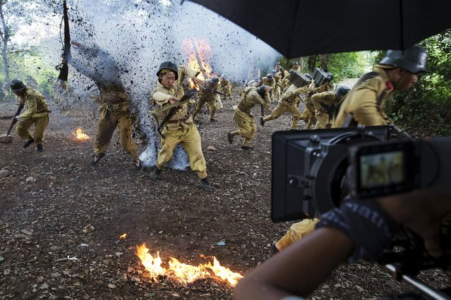 """The camera rolls as actors dressed as historical Chinese soldiers act as though they have been hit by artillery fire, during filming of """"The Last Prince"""" television series at Hengdian World Studios in Hengdian July 24, 2015. (Photo by Damir Sagolj/Reuters)"""