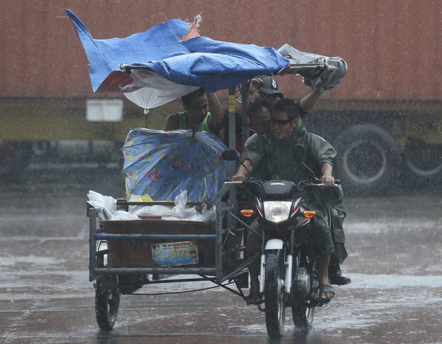 Workers at a nearby fishing port brave strong rains as Typhoon Rammasun batters suburban Navotas, north of Manila,  Philippines on Wednesday, July 16, 2014. Typhoon Rammasun knocked out power in many areas but it spared the Philippine capital, Manila, and densely-populated northern provinces from being directly battered Wednesday when its fierce wind shifted slightly away, officials said. (Photo by Aaron Favila/AP Photo)