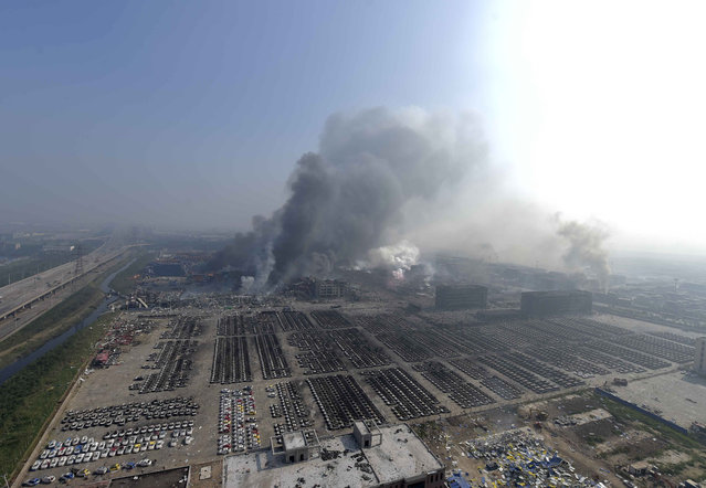 In this photo released by China's Xinhua News Agency, smoke rise from the site of explosions from a nearby building in the Binhai New Area in northeastern China's Tianjin municipality, Thursday, August 13, 2015. (Photo by Yue Yuewei/Xinhua via AP Photo)