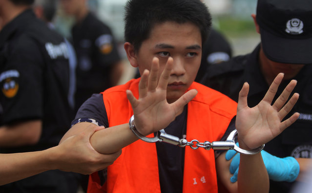 A suspect of telecom fraud is escorted by China police SWAT team and a Cambodian police as they were deported to China at the International Airport of Phnom Penh, June 24, 2016. (Photo by Samrang Pring/Reuters)