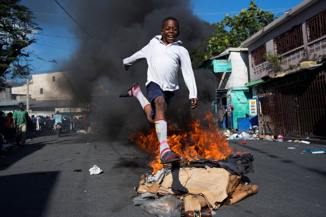 """A boy jumps a barricade in flames near the Petionville market, during a protest day in Port-au-Prince, Haiti, 17 October 2019. Port-au-Prince woke up with numerous barricades, roadblocks and intentional fires at the start of a new mobilization day called by opposition groups against President Jovenel Moise. The mobilization day has been raised by the opposition as a day of """"general uprising"""" of the popular and peasant classes against the head of state. (Photo by Orlando Barria/EPA/EFE)"""