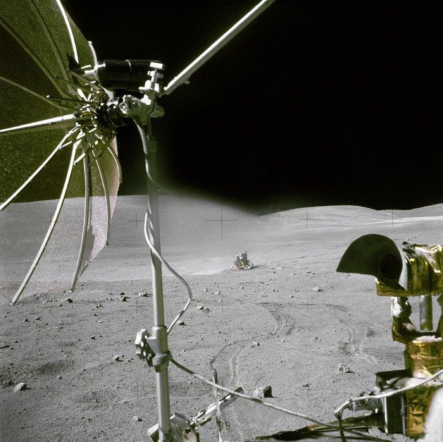 "The Apollo 16 Lunar Module ""Orion"" is photographed from a distance by astronaut Chares M. Duke Jr., Lunar Module pilot, aboard the moving Lunar Roving Vehicle. Astronauts Duke and Commander John W. Young, were returing from the third Apollo 16 extravehicular activity (EVA-2). The RCA color television camera mounted on the LRV is in the foreground. A portion of the LRV's high-gain antenna is at top left. (Photo by NASA)"