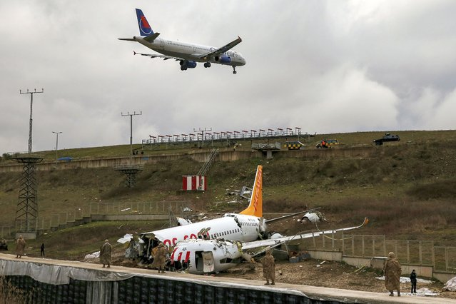 A plane descends to land, as soldiers guard the wreckage of a plane operated by Pegasus Airlines after it skidded Wednesday off the runway at Istanbul's Sabiha Gokcen Airport, in Istanbul, Thursday, February 6, 2020. Flights resumed Thursday after the airliner skidded off a runway, killing three people and injuring dozens. The Boeing 737 landed during strong winds and heavy rain and overshot the runway. It skidded about 50-60 meters (yards) before it dropped into the ditch from a height of about 30 meters (98 feet). (Photo by Emrah Gurel/AP Photo)