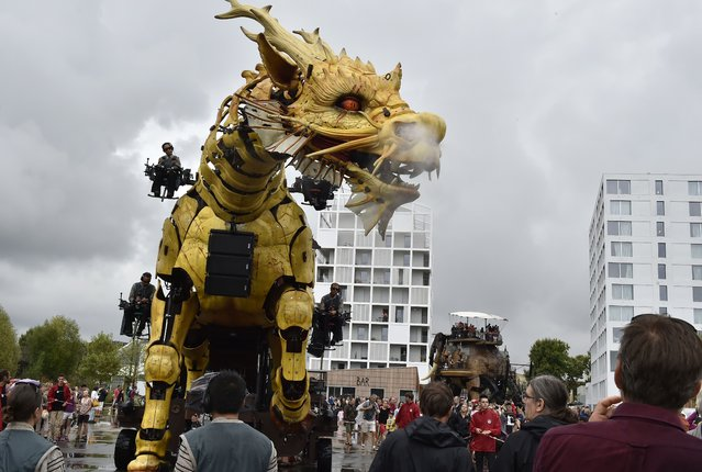 People look at the mechanical Horse Dragon Long Ma as part of its return from China on August 14, 2015, to the worskhops of La Machine, a French production company in Nantes. The Horse Dragon was created in 2014 by La Machine to celebrate the 50th anniversary of diplomatic relations between France and China. (Photo by Georges Gobet/AFP Photo)