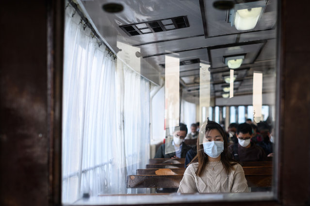 Passengers wear face masks, as a preventative measure against the COVID-19 coronavirus, as they travel on a ferry from Hong Kong island to Koloon side of Hong Kong on February 12, 2020. The death toll from the COVID-19 coronavirus epidemic climbed past 1,100 on February 12 but the number of new cases fell for a second straight day, raising hope the outbreak could peak later this month. (Photo by Philip Fong/AFP Photo)