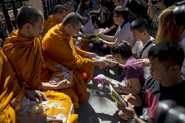 Family members of Malaysians victims pay their respect to Buddhist monks during a Buddhist ceremony at the site at Erawan shrine, in central Bangkok, Thailand, August 19, 2015. Thai police said on Wednesday they had still not established the nationality or whereabouts of the man they suspect bombed the Bangkok shrine, killing at least 20 people, suggesting the trail had gone cold after he was captured by CCTV at the scene. (Photo by Athit Perawongmetha/Reuters)