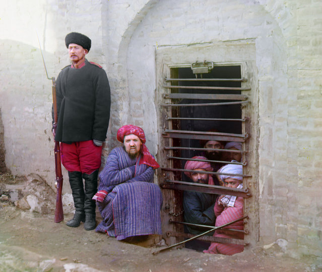 Photos by Sergey Prokudin-Gorsky. Zindan (prison), with inmates looking out through the bars and a guard with Russian rifle, uniform, and boots, Central Asia. Russia, Emirate of Bukhara, Bukhara area, 1907