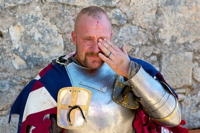 """Teams train for months to compete in hand-to-hand medieval combat. The fighting, and the injuries, are real. A USA Knight team member is seen here resting after combat during the International Medieval Combat at the castle of Belmonte, May 4, 2014, in Belmonte, Spain. """"I've seen guys take helmets off and there's no teeth left, their nose is broke, their heads gashed open, they're bleeding all over"""", said a member of the USA Knights team. (Photo by Juan Naharro Gimenez/Getty Images)"""