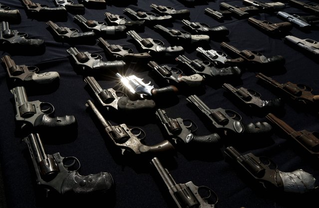 Pistols are displayed by police before their destruction in Panama City, Wednesday, August 6, 2014. Panama's police destroyed a hundred of weapons handed over during the first month of the new government, most of them without a gun license and used in criminal activities. Panama's President Juan Carlos Varela announced an amnesty to allow gang members surrender their weapons. (Photo by Arnulfo Franco/AP Photo)
