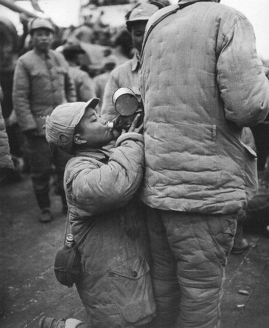 1948年11月, 上海,从北方前线撤下的一童军喝着同伴水壶里的水。 (In November 1948, Shanghai, removed from the northern front of a Scout drinking companion kettle of water)