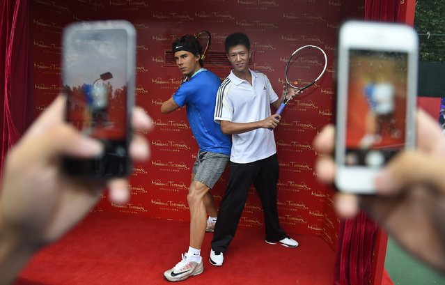 A man poses for pictures with a wax statue of Spain's tennis player Rafael Nadal during a Madame Tussauds' unveiling ceremony at a tennis court in Wuhan, Hubei province, August 13, 2014. (Photo by Reuters/Stringer)