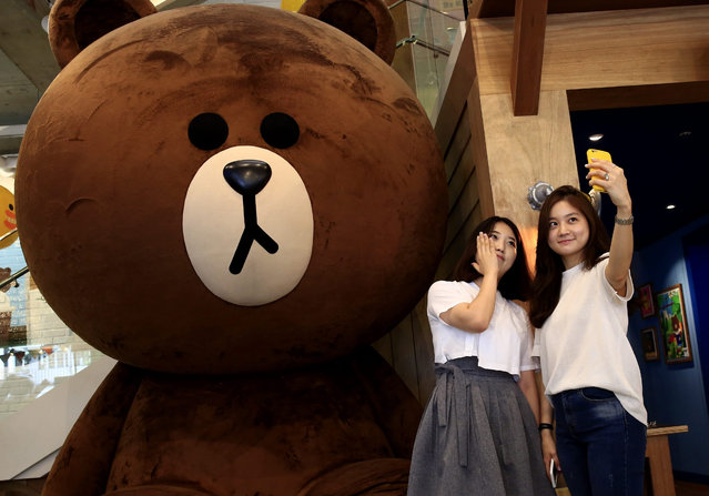 "Visitors take a selfie next to a big-scale stuffed toy of ""Brown"", a character from the Line Corp. messaging application, at a Line Friends flagship store in the Itaewon district of Seoul, South Korea, 15 July 2016. Line, a subsidiary of South Korean Internet Company Naver Corp., was listed on the First Section of the Tokyo Stock Exchange on 15 July 2016. It began trading on at 3,300 yen (around 32 US dollar) per share, making it this year's highest tech initial public offering (IPO) so far in Japan, media reported. The shares of the Japanese messaging-app operator rose 51.5 percent during Friday's trading on the Tokyo Stock Exchange after making its debut on Wall Street the previous day. (Photo by Jeon Heon-Kyun/EPA)"