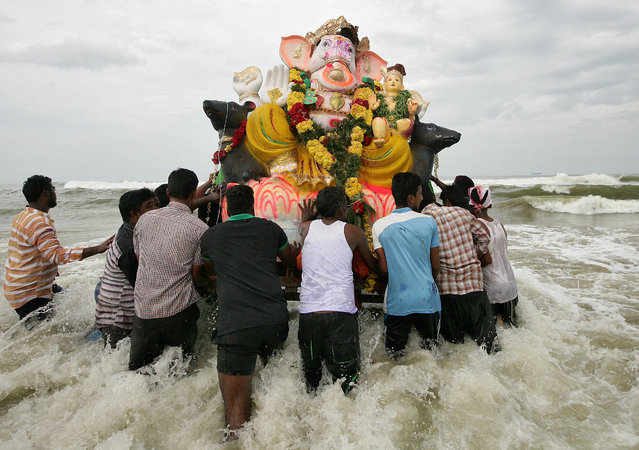 Devotees carry an idol of the Hindu god Ganesh, the deity of prosperity, into the Bay of Bengal for its immersion during the ten-day-long Ganesh Chaturthi festival in Chennai, August 27, 2017. (Photo by P. Ravikumar/Reuters)