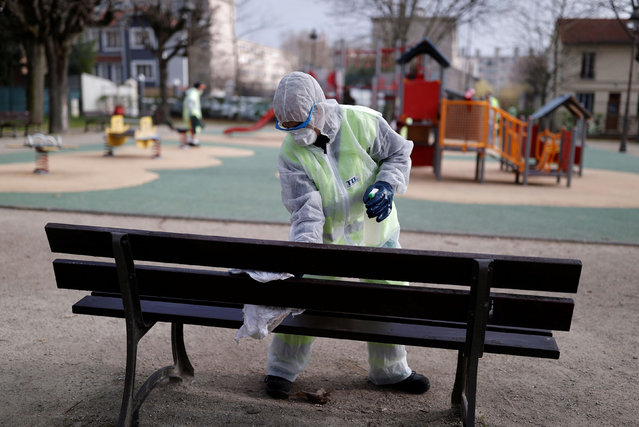 A worker cleans a bench with disinfectant at a children's playground to slow the rate of the coronavirus disease (COVID-19) in Suresnes, near Paris, March 20, 2020. (Photo by Christian Hartmann/Reuters)