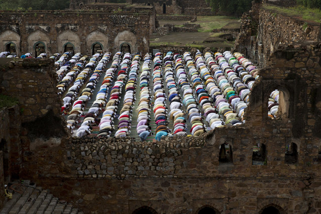 """Indian Muslims offer Eid al-Adha prayers at the 14th century Feroz Shah Kotla Jami Mosque in New Delhi, India, Saturday, September 2, 2017. Muslims worldwide are celebrating Eid al-Adha, or """"Feast of Sacrifice"""", that commemorates the willingness of the Prophet Ibrahim to sacrifice his son. Muslims slaughter livestock and distribute part of the meat to the poor. (Photo by Tsering Topgyal/AP Photo)"""