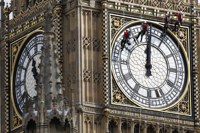 Workers hang outside the clock face as they clean the Big Ben clocktower of the Houses of Parliament in London, Monday, August 18, 2014. (Photo by Sang Tan/AP Photo)