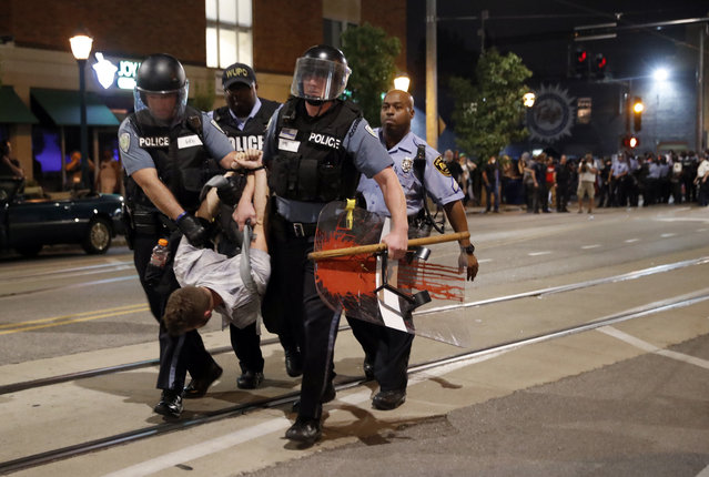 Police arrest a man as they try to clear a violent crowd Saturday, September 16, 2017, in University City, Mo. Earlier, protesters marched peacefully in response to a not guilty verdict in the trial of former St. Louis police officer Jason Stockley. (Photo by Jeff Roberson/AP Photo)