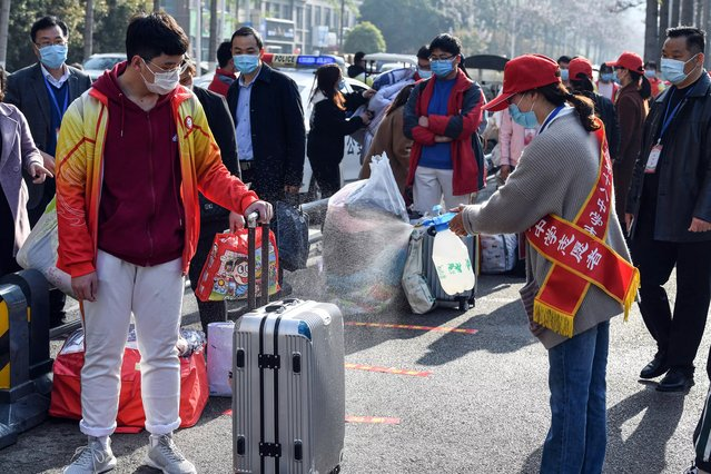A volunteer sprays disinfectant on the luggage of a student as high school grade three students return after the term opening was delayed due to the COVID-19 coronavirus outbreak, in Bozhou in China's eastern Anhui province on April 7, 2020. China on April 7 reported no new coronavirus deaths for the first time since it started publishing figures in January, the National Health Commission said. (Photo by AFP Photo/China Stringer Network)