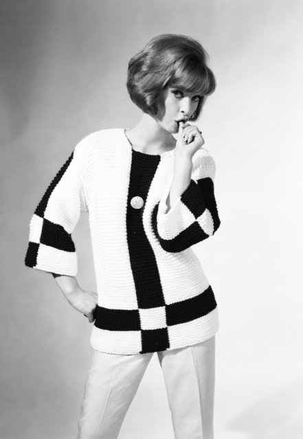 Sucks. A woman wearing a jumper in contrasting colours sucks her thumb suggestively. 27th July 1962. (Photo by Chaloner Woods)