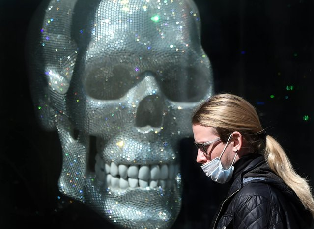 A man wearing a face mask, amid concerns over the spread of the novel coronavirus COVID-19, walks past a fashion boutique shop window decorated with a skull in the center of the Ukrainian capital of Kiev on April 9, 2020. (Photo by Sergei Supinsky/AFP Photo)