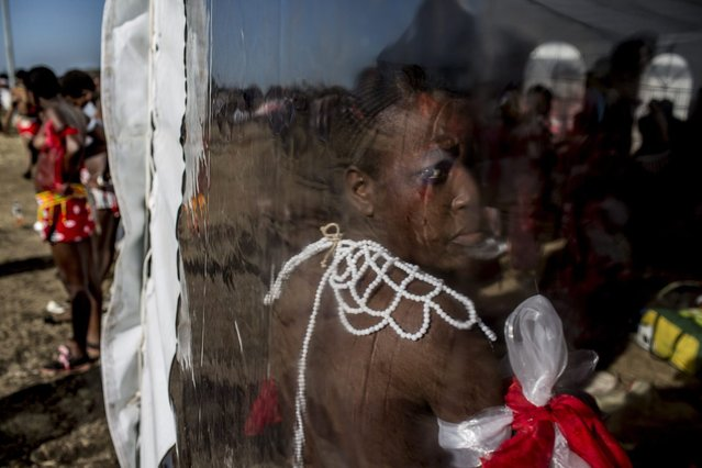 A South African maiden looks from inside a marquee as she prepare herself for the Reed Dance ceremony on September 5, 2014 at the eNyokeni Royal Palace in Nongoma in the KwaZulu-Natal region, ahead of the 13th anniversary of the Reed Dance (uMkhosi woMhlanga) celebrated by the Zulu King, Goodwill Zwelithin. (Photo by Marco Longari/AFP Photo)
