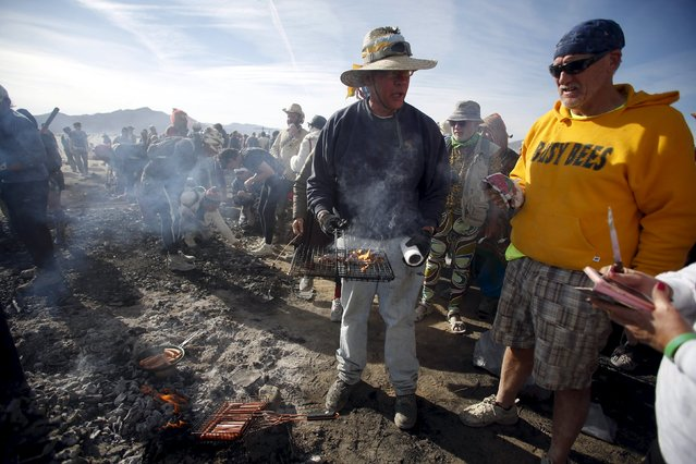 """Eric Ruud (L) and Don Clark cook breakfast on the smoldering remains of the Man during the Burning Man 2015 """"Carnival of Mirrors"""" arts and music festival in the Black Rock Desert of Nevada September 5, 2015. (Photo by Jim Urquhart/Reuters)"""