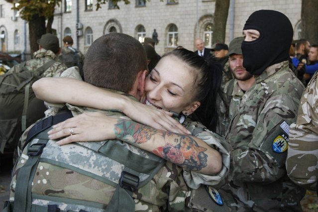 "A woman embraces her friend, a volunteer of Ukrainian self-defence battalion ""Azov"", who returned the front line in the eastern regions of Ukraine, in Kiev September 15, 2014. (Photo by Valentyn Ogirenko/Reuters)"