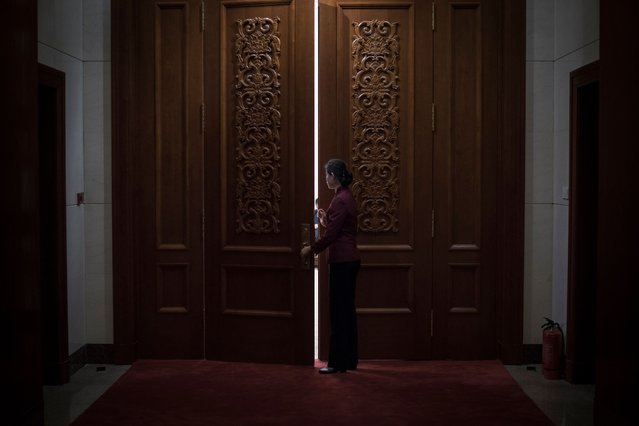 A hostess closes the door of a meeting room at the Great Hall of the People during the Communist Party's 19th Congress in Beijing on October 19, 2017. The Chinese Communist Party opens its week-long, twice-a-decade congress on October 18 at the Great Hall of the People. (Photo by Fred Dufour/AFP Photo)
