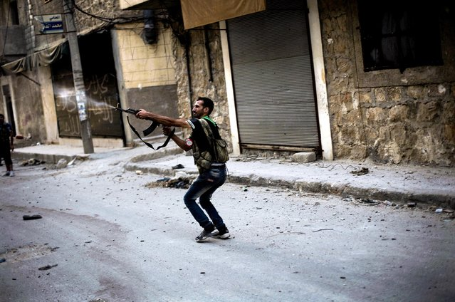 Free Syrian Army fighter fires his weapon against Syrian Army positions in the Amariya district in Aleppo, Syria, on September 19, 2012. (Photo by Manu Brabo/Associated Press)