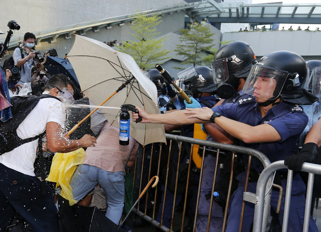 A riot policeman uses pepper spray during clash with protesters, as tens of thousands of protesters block the main street to the financial Central district outside the government headquarters in Hong Kong, September 28, 2014. (Photo by Tyrone Siu/Reuters)
