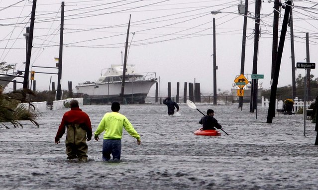 People wade and paddle down a flooded street as Hurricane Sandy approaches in Lindenhurst, N.Y. (Photo by Jason DeCrow/Asociated Press)