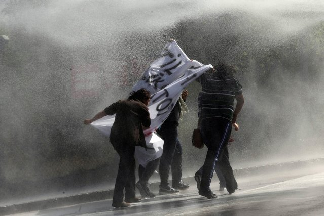 Demonstrators hold a banner as as they are sprayed by a water cannon during clashes with riot police outside of the Middle Eastern Technical University (METU) in Ankara on October 9, 2014 during a protest to denounce Turkey's unwillingness to intervene militarely against Islamic State (IS) forces in the Syrian town of Ain al-Arab, known as Kobane by the Kurds. (Photo by Adem Altan/AFP Photo)