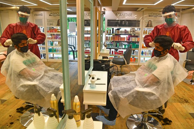 Staff at Shiva's Signature hair salon wearing Personal Protective Equipment (PPE) suit and face shield attends a customer after personal grooming services were allowed to resume following relaxation of lockdown norms amidst Covid-19 coronavirus pandemic, in Mumbai on June 28, 2020. India now has more than 500,000 confirmed coronavirus cases, according to government figures released on June 27 that showed a record daily leap of 18,500 new infections. (Photo by Indranil Mukherjee/AFP Photo)