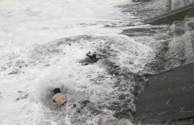 A man, bottom jumps into the water to rescue a woman, center, who fell due to strong tidal waves on the Bay of Bengal coast at Gopalpur, Orissa, about 285 kilometers (178 miles) north east of Visakhapatnam, India, Sunday, October 12, 2014. (Photo by Biswaranjan Rout/AP Photo)