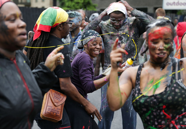 Revellers dance and spray paint, a traditional way of starting the carnival on the first day of the Notting Hill Carnival in west London on August 28, 2016. (Photo by Daniel Leal-Olivas/AFP Photo)