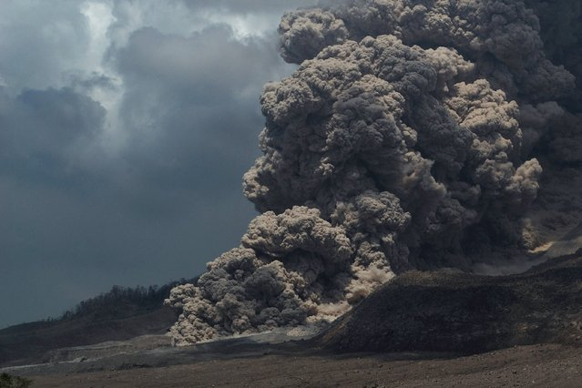 Super heated giant ash cloud spew from the crater of Mount Sinabung volcano threatening villages during an eruption on October 17, 2014 as seen from Simpang Empat district on Sumatra island. In February, Sinabung's eruption killed about 17 people and forced more than 33,000 others to flee their homes. (Photo by Sutanta Aditya/AFP Photo)