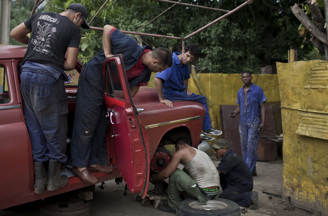 In this October 16, 2014 photo, men repair coil spring of a classic American car in Havana, Cuba. The cars may gleam on the outside, but they're often battered, rolling monuments to ingenuity within. People fabricate parts in crude workshops. (Photo by Franklin Reyes/AP Photo)