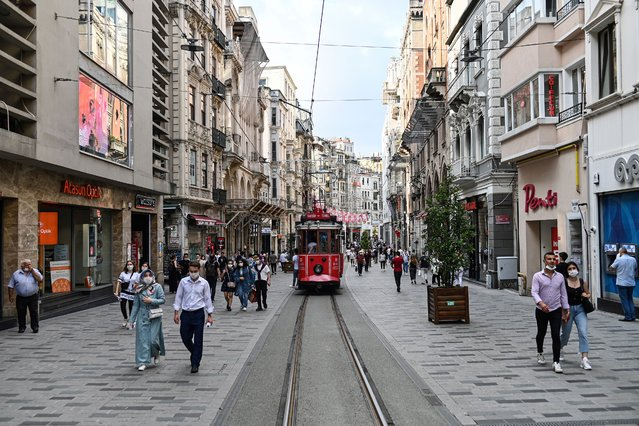 People wearing protective face masks to curb the spread of the novel coronavirus (COVID-19) walk past a tramway in popular shopping avenue Istiklal, in Istanbul on June 25, 2020. Turkey, a nation of some 83 million, has removed most restrictions, reopened restaurants and resumed mass prayers but officials have warned against complacency. Turkey's daily infections have risen in recent weeks to over a thousand, and authorities have made face masks mandatory in public in several cities including Istanbul. (Photo by Ozan Kose/AFP Photo)