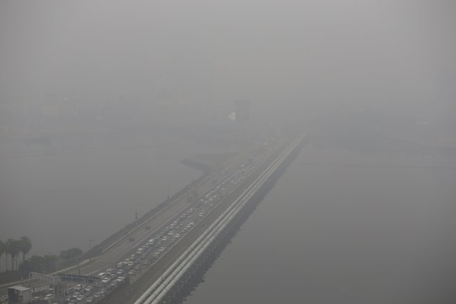 A view of the vehicles plying the causeway to Malaysia shrouded by haze in Singapore September 29, 2015. The 3-hour haze Pollutant Standards Index (PSI) reached a high of 173 at 8am on Tuesday, according to the National Environment Agency. Slash-and-burn agriculture in neighboring Indonesia has blanketed Singapore in a choking haze for weeks. (Photo by Edgar Su/Reuters)