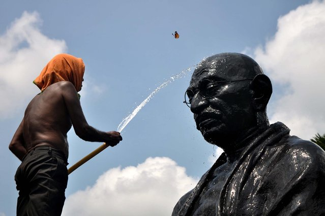 A butterfly flutters as an Indian labourer showers water onto a statue of Mahatma Gandhi on the eve of Gandhi Jayanti at Gandhi Park in the eastern city Bhuabenswar on October 1, 2015. Gandhi Jayanti is also observed as International Day of Non-Violence and is celebrated in India to mark the occasion of the birth anniversary of Mahatma Gandhi, the Father of the Nation on October 2 annually. (Photo by Asit Kumar/AFP Photo)