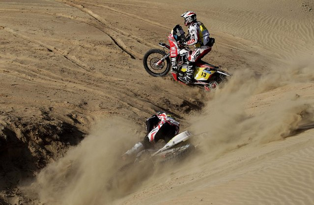 Husqvarna rider Alessandro Botturi of Italy falls from his motorcycle as Honda rider Gerard Farres Guell of Spain races past him in the 3nd stage of the race. (Photo by Victor R. Caivano/Associated Press)