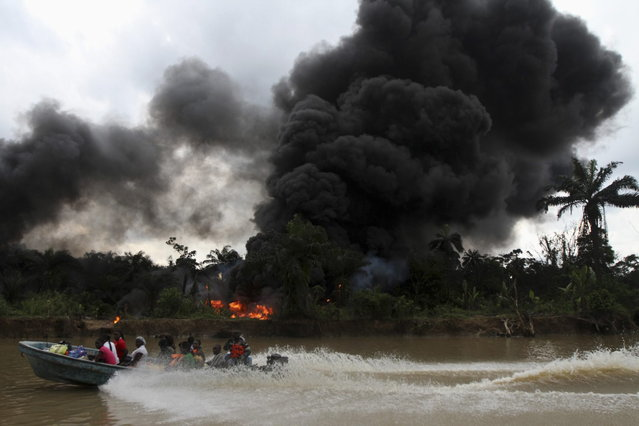 A passenger speedboat churns up the water, while in the background an illegal oil refinery is left burning after a military chase had occurred earlier in a windy creek near river Nun in Nigeria's oil state of Bayelsa December 6, 2012. (Photo by Akintunde Akinleye/Reuters)