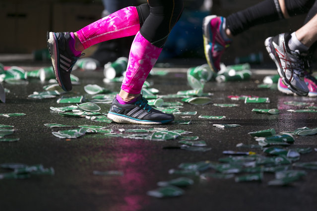 Runners step on used water cups dumped in the street during the 44th annual New York City Marathon in New York, Sunday, November 2, 2014. (Photo by Gordon Donovan/Yahoo News)